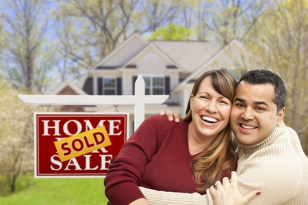 purchase: Happy Mixed Race Couple in Front of Sold Home For Sale Real Estate Sign and House. Stock Photo