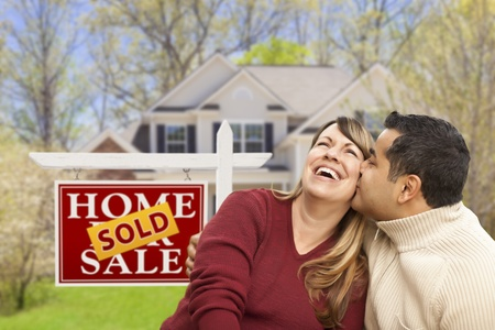 Happy Mixed Race Couple in Front of Sold Home For Sale Real Estate Sign and House. Stock Photo - 19249324