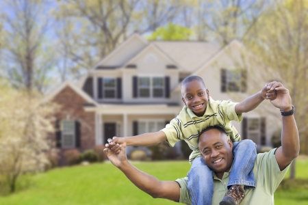 real estate house: Playful African American Father and Son In Front Yard of Home.