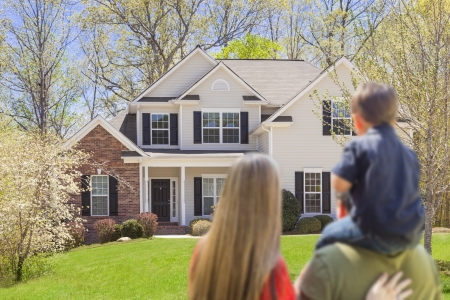 Mixed Race Young Family Looking At Beautiful New Home.