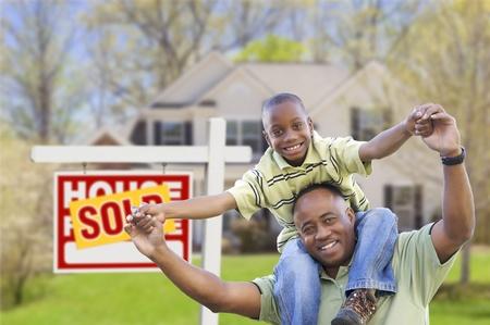 real estate sold: Feliz padre afroamericano e hijo en frente de casa nueva y signo de inmuebles vendidos.