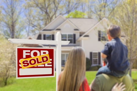real estate house: Curious Family Facing Sold For Sale Real Estate Sign and Beautiful New House.