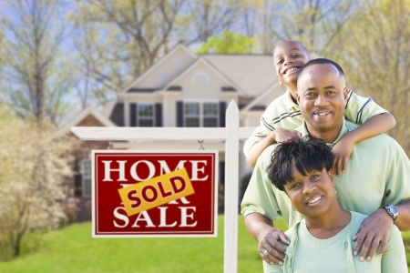 selling house: Happy African American Family In Front of Sold Real Estate Sign and House.
