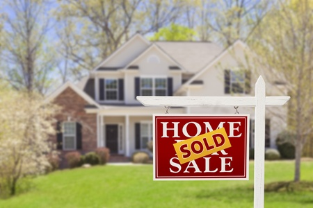 real estate: Sold Home For Sale Real Estate Sign and Beautiful New House. Stock Photo