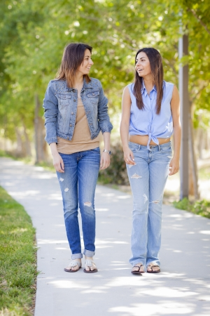two people talking: Young Adult Mixed Race Twin Sisters Walking Together Outside. Stock Photo