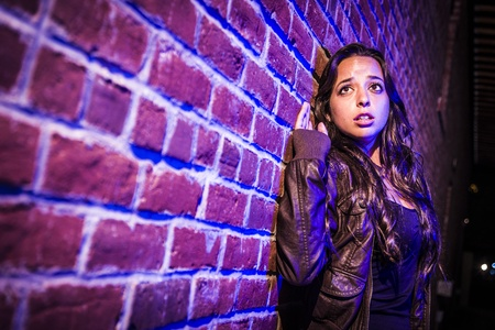 escape: Frightened Pretty Young Woman Against a Brick Wall at Night.