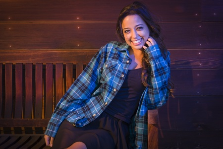 lustrous: Portrait of a Pretty Mixed Race Young Adult Woman Sitting on Wooden Bench Against a Lustrous Wood Wall Background.