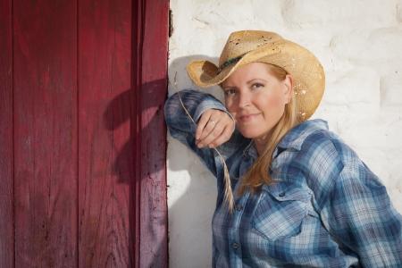 adobe wall: Bella Cowgirl Indossando cappello del cowboy Pendente Contro Vecchio Adobe muro e Red Door.