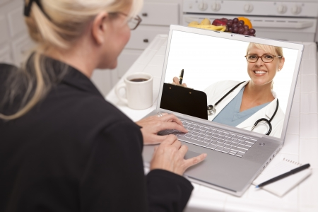 Woman In Kitchen Using Laptop having Online Chat with Doctor on Screen. photo