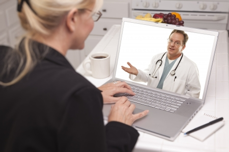 chat: Woman using Laptop having Online Chat with Doctor on Screen. Stock Photo