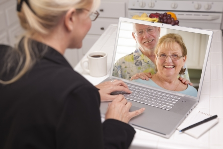 Woman Using Laptop having Online Chat with Senior Couple or Parents On Screen. photo