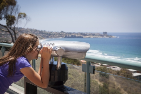 Young Girl Looking Out Over the Pacific Ocean and La Jolla, California with Telescope. Stock Photo - 20671709