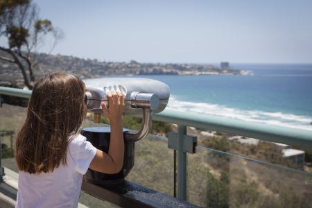 Young Girl Looking Out Over the Pacific Ocean and La Jolla, California with Telescope. Stock Photo - 20671710