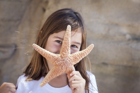 sedentary: Young Pretty Girl Playing with Starfish. Stock Photo