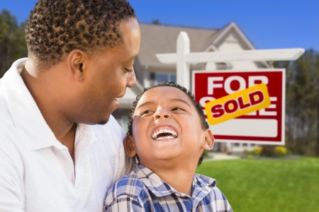 american house: Happy Mixed Race Father and Son In Front of Sold Real Estate Sign and New House