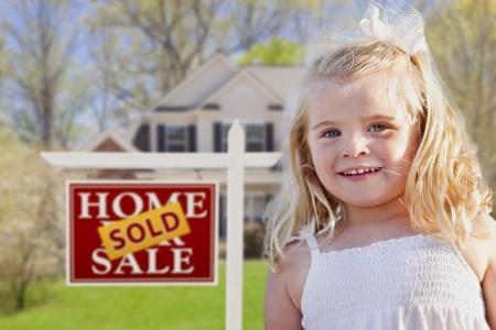 Sonriente Niña linda en patio delantero con Vendido Venta de Bienes Raíces y la Cámara Suscribirse Foto de archivo