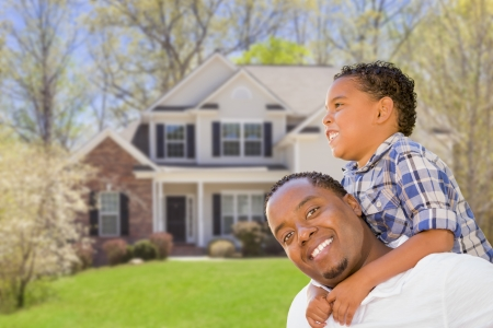 Happy Playful African American Father and Mixed Race Son In Front of House  photo