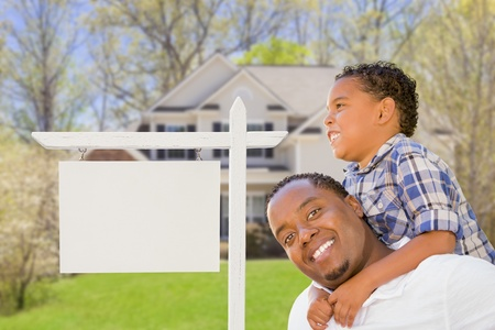 Happy African American Father and Mixed Race Son In Front of Blank Real Estate Sign and New House  photo