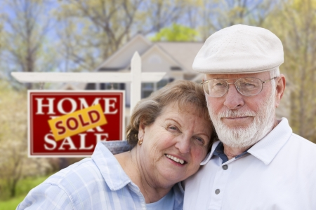 Glückliche liebevolle ältere Paare, die vor verkauftem Real Estate-Zeichen und -haus umarmen Standard-Bild