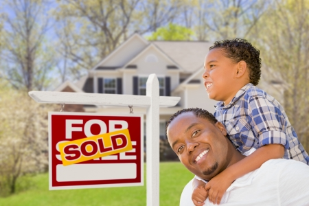 Happy Mixed Race Father and Son In Front of Sold Real Estate Sign and New House  photo