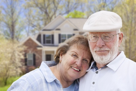 Attractive Happy Senior Couple in Front Yard of House. photo