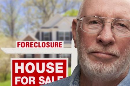 抵当流れの不動産の看板と家の前で落ち込んでいる年配の男性人。