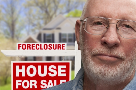 foreclosure: Depressed Senior Man in Front of Foreclosure Real Estate Sign and House.