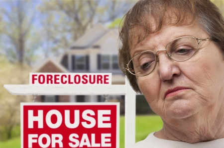Depressed Senior Woman in Front of Foreclosure Real Estate Sign and House. photo