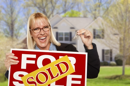 Happy Young Woman with Sold For Sale Real Estate Sign and Keys in Front of House. Standard-Bild