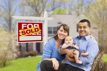 Happy Mixed Race Young Family in Front of Sold Home For Sale Real Estate Sign and House. photo
