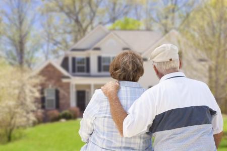jubilados: Pares mayores felices de detr�s Mirando frente de la casa. Foto de archivo
