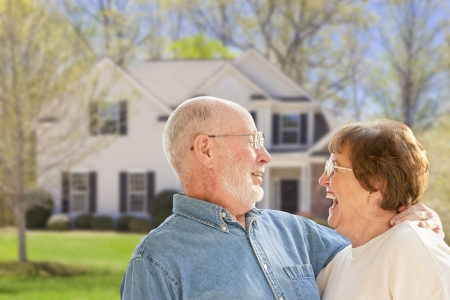 house: Happy Senior Couple in the Front Yard of Their House.
