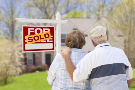 retirement age: Happy Affectionate Senior Couple Hugging in Front of Sold Real Estate Sign and House. Stock Photo