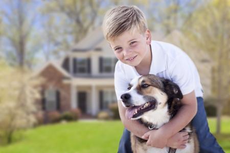 幸せな少年と彼の犬が彼らの家の前の庭で。