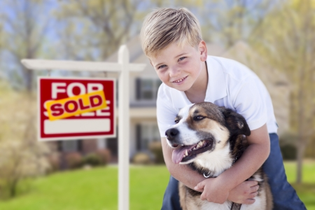 home sale: Happy Young Boy and His Dog in Front of Sold For Sale Real Estate Sign and House.