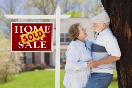 Sold Real Estate Sign with Happy Affectionate Senior Couple Hugging in Front of House. Stock Photo - 20758461