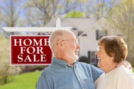 Happy Senior Couple Front of For Sale Real Estate Sign and House. photo
