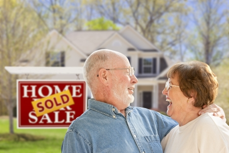 sales person: Happy Affectionate Senior Couple Hugging in Front of Sold Real Estate Sign and House. Stock Photo