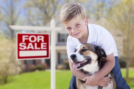 Happy Young Boy and His Dog in Front of For Sale Real Estate Sign and House. Stock Photo