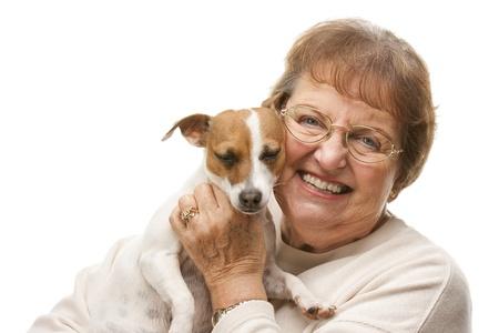companionship: Feliz mujer atractiva Superior con Puppy Aislado en un fondo blanco.