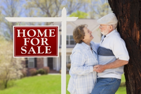 Happy Senior Couple Front of For Sale Real Estate Sign and House. Stock Photo - 20758468