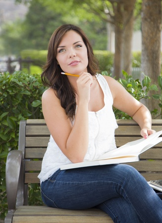 Attractive Young Adult Female Student on Bench Outdoors with Books and Pencil. photo