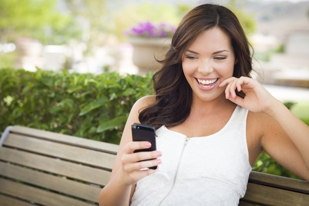 Attractive Smiling Young Adult Female Texting on Cell Phone Outdoors on a Bench. photo