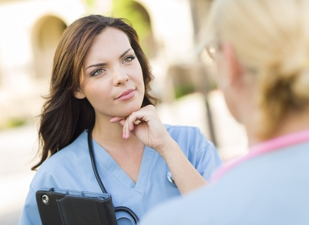 nurse practitioner: Two Young Adult Professional Female Doctors or Nurses Talking Outside. Stock Photo
