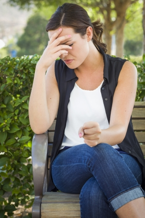 caras tristes: Malestar mujer joven que se sienta solamente en banco fuera con la cabeza en la mano y el pu�o apretado.