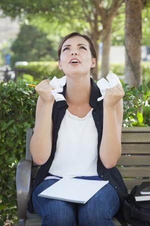 Gefrustreerd en Verstoor Jonge Vrouw met Potlood en verfrommeld papier in haar handen zittend op bankje buiten.