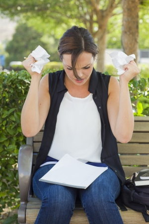 writers block: Frustrated and Upset Young Woman with Pencil and Crumpled Paper in Her Hands Sitting on Bench Outside.