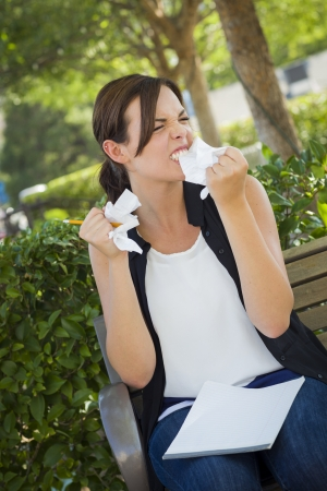 Frustrated and Upset Young Woman with Pencil and Crumpled Paper in Her Hand Sitting on Bench Outside. Stock Photo