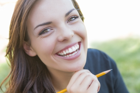 school of life: Portrait of Pretty Young Female Student with Pencil on Campus Lawn. Stock Photo