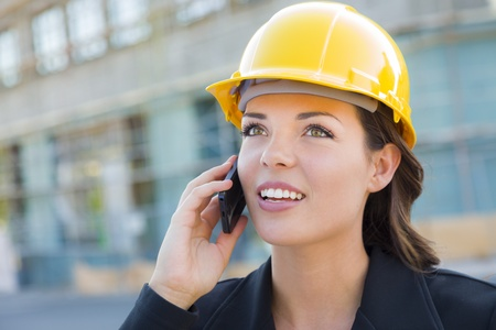 helmet construction: Young Professional Female Contractor Wearing Hard Hat at Contruction Site Using Cell Phone. Stock Photo